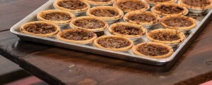 "A tray of small, or ""penny"", pecan pie tins sits on a wooden picnic table."