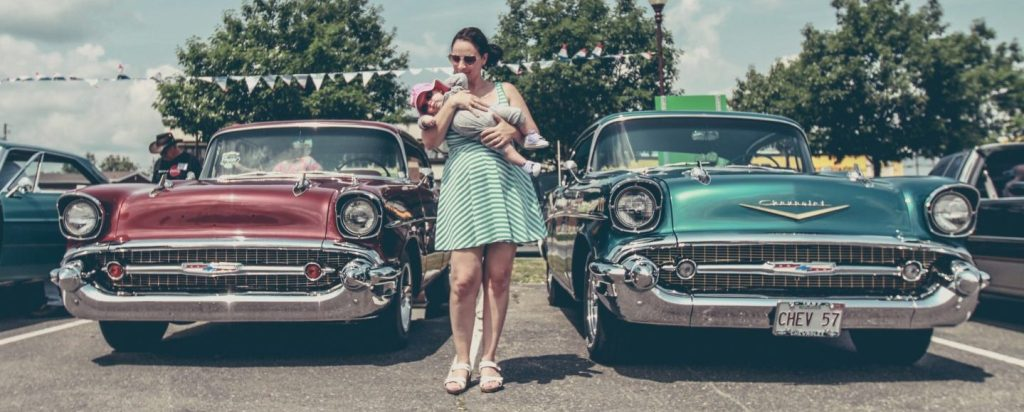 A woman in a teal romper carries her child between two vintage, '57 Chevys.
