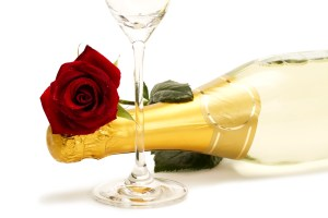 wet red rose on a champagne bottle behind a champagne glass