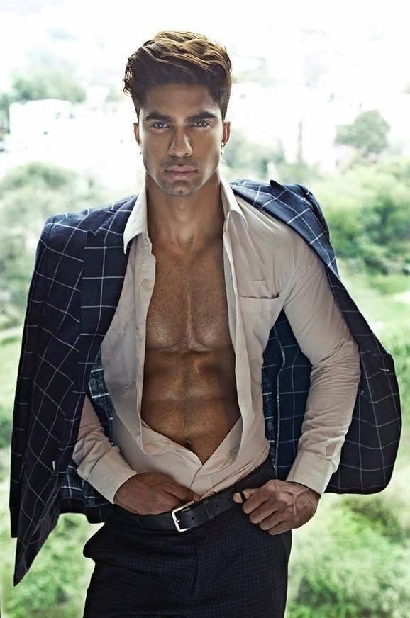 Handsome man in open shirt with hand in pants and blazer over shoulders