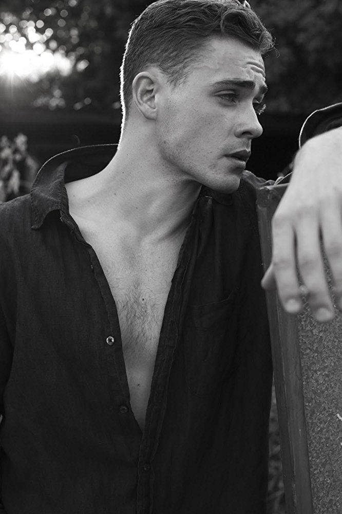 Dacre Montgomery shirt slightly open looking away