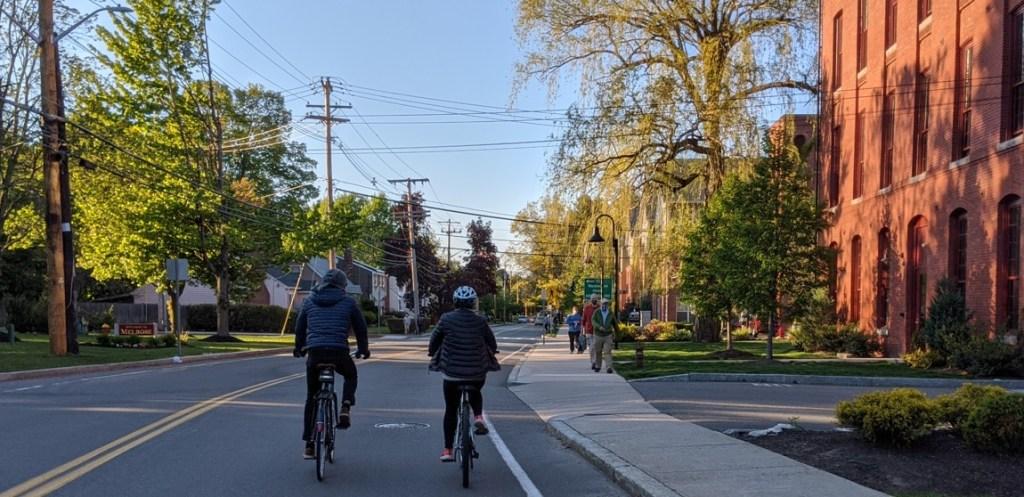 People walking and biking along Washington Street at the Melrose border