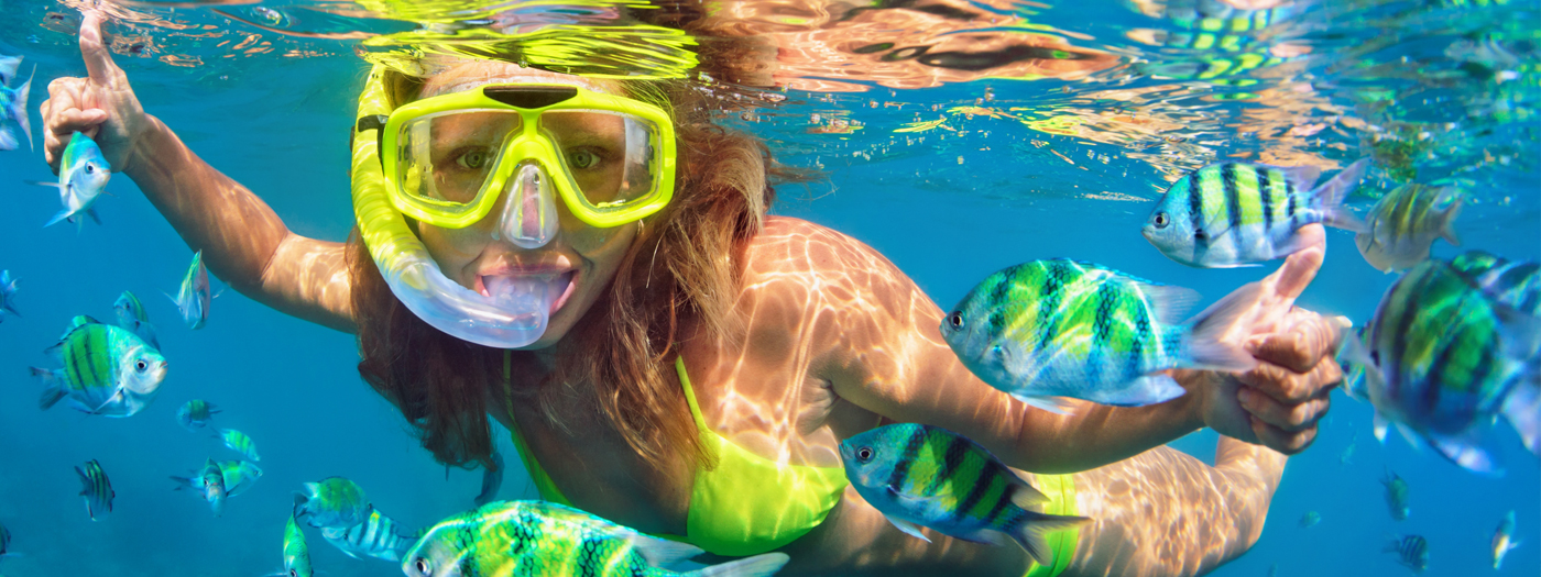 Teenage girl snorkeling with exotic fish and giving a double thumbs up