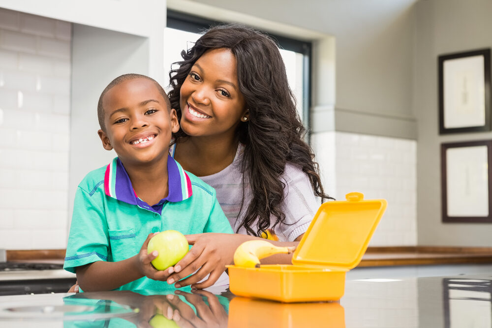 Happy mom and child pose with fruit from a packed lunch