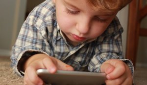 toddler playing on a mobile phone