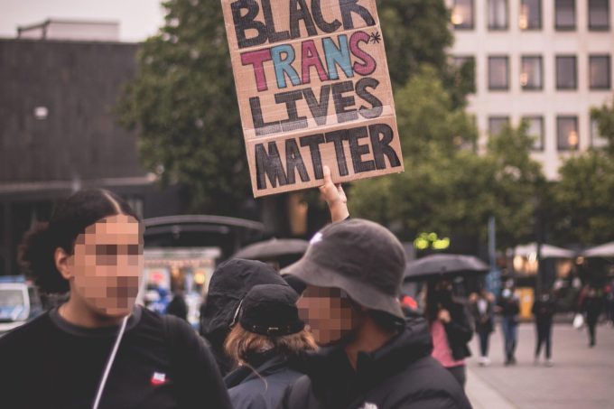 """Two people talking with a sign above them that says """"Black Trans Lives Matter"""""""