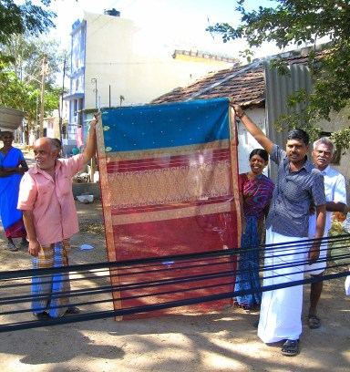 12.3 men holding up sari beside warp