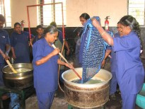 9.1 two women taking a cloth out of dye pot