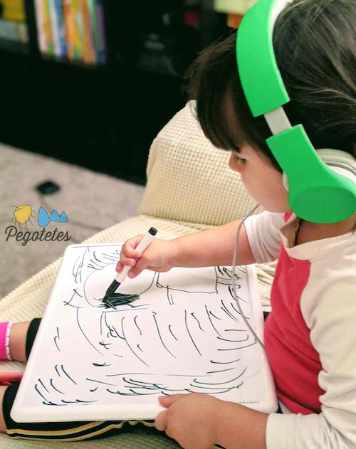 niña escuchando audiocuentos y pintando