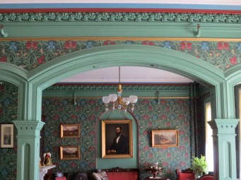 The center of the triple arch which bisects the 1st-floor drawing rooms. Note the moulding, and the portrait of Henry Cundall hanging at the far end. Photo credit: M.W. Ferris Photography