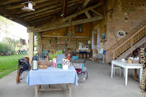Une grande cours couverte avec une immense table en bois qui invite à la convivialité et au partage © Fabienne Bodan