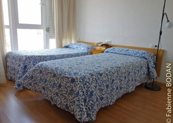 Chambre à 3 lits individuels, ici les 2 premiers. Derrière cette porte, la chambre. Hostal Puente Romano, Monforte de Lemos, Camino del Invierno © Fabienne Bodan