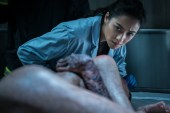 Megan (Shay Mitchell) observes the gruesome condition of Hannah Grace's body in Screen Gems' THE POSSESSION OF HANNAH GRACE.
