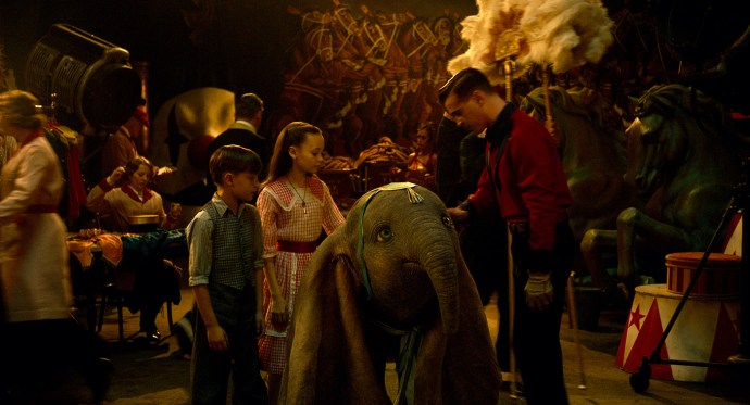 """ON WITH THE SHOW – When a persuasive entrepreneur decides to make Dumbo a star at his larger-than-life entertainment venture, former circus star Holt Farrier (Colin Farrell) and his children Milly (Nico Parker) and Joe (Finley Hobbins) vow to stick with their beloved flying elephant the whole way. Directed by Tim Burton, Disney's all-new, live-action, big-screen adventure """"Dumbo"""" flies into theaters on March 29, 2019. ©2018 Disney Enterprises, Inc. All Rights Reserved."""