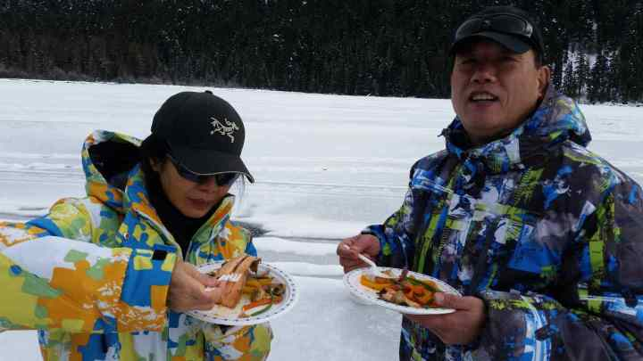 Clients enjoy a tasty lunch while Ice fishing in British Columbia Canada