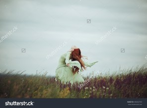 stock-photo-young-redhead-girl-in-medieval-dress-walking-through-field-with-sage-flowers-wind-concept-fantasy-438462703