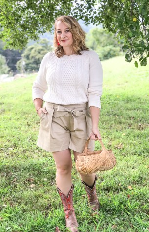 Transition summer staples to fall: woman under apple tree in fall transition outfit of cable knit sweater, shorts, and cowboy boots