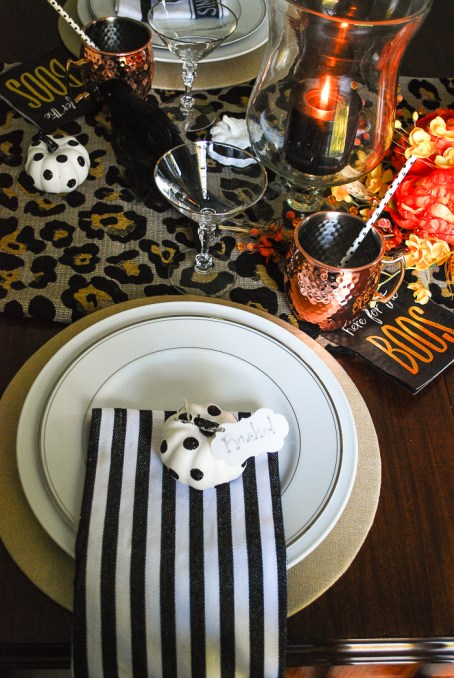 Glam Halloween table set with copper mugs, leopard print runner, dramatic orange and yellow florals, glass pumpkins, and spooky crows.