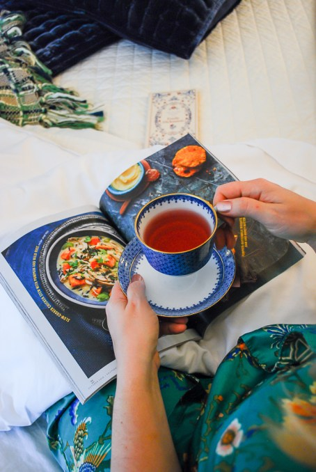 Warm cozy evening in comfy bed with cup of tea and magazine