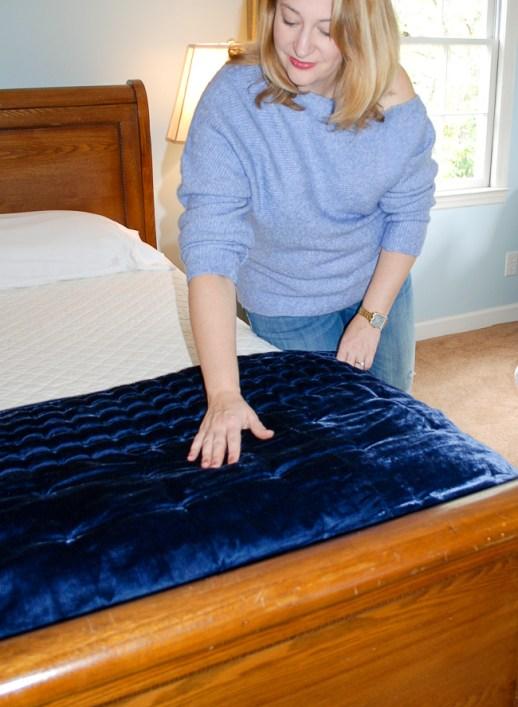Woman lays blue velvet comforter on bed