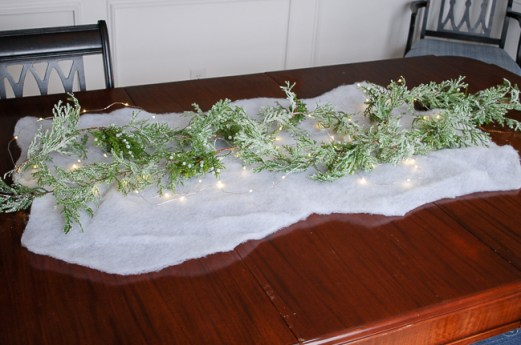Winter tablescape tutorial - laying down cedar garland