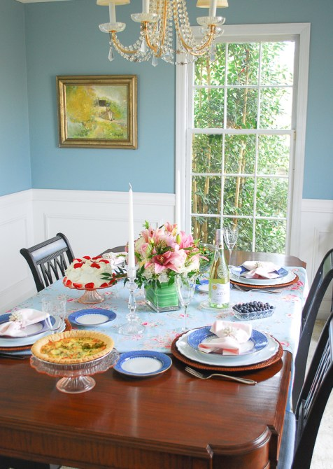 A spring table setting in pink and blue to freshen up the dining room with romantic florals, blue lace china, and gingham napkins.
