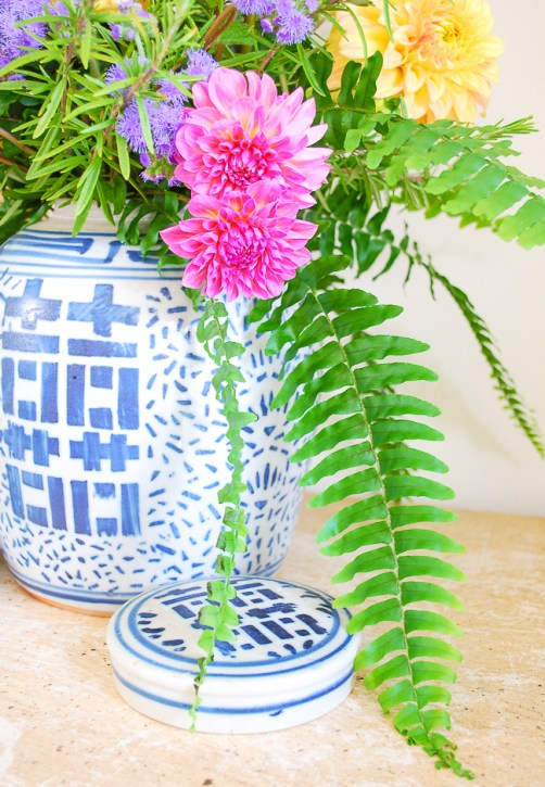 Detail view of pink dahlias and sweeping fern down side of ginger jar