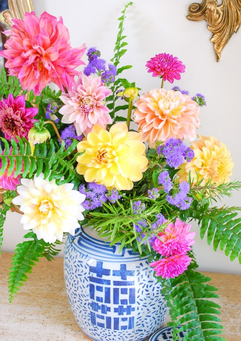 a blue and white ginger jar filled with pink and yellow dahlias, fern, and rosemary