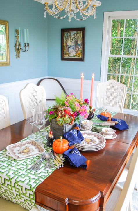 A traditional dining room set with a Southern autumn table featuring mini pumpkins, fall themed china, candle light, and monogrammed napkins