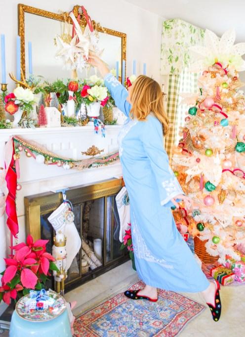 Katherine in blue caftan tweaks paper star lantern hanging from mirror