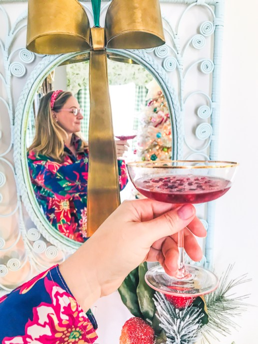 Katherine of Pender & Peony in mirror above holiday bar cart drinking a pomegranate cocktail