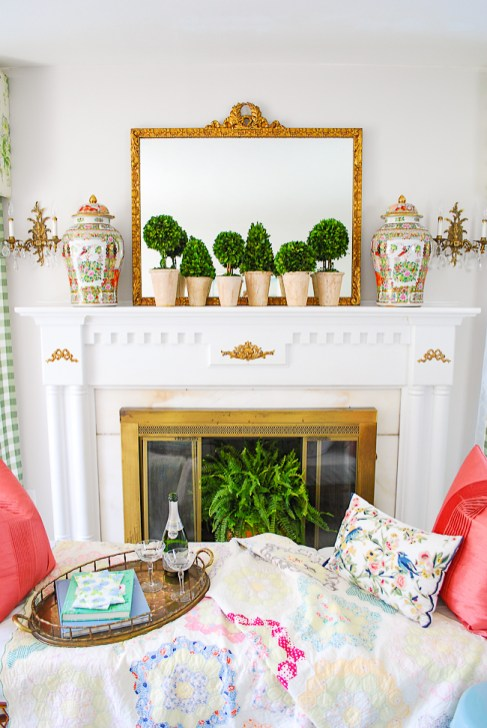 Grandmillennial mantel decor with boxwood topiaries, rose medallion temple jars, and gilt mirror