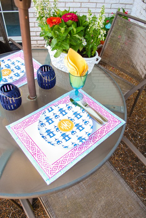 colorful summer decorating idea - patio table set with pink and blue Indian block print placemats, monogrammed pagoda plates, and zinnias