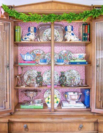 Updated china cabinet with wallpaper backing and shelves styled with vintage and antique tableware, dishes, decor, and silver
