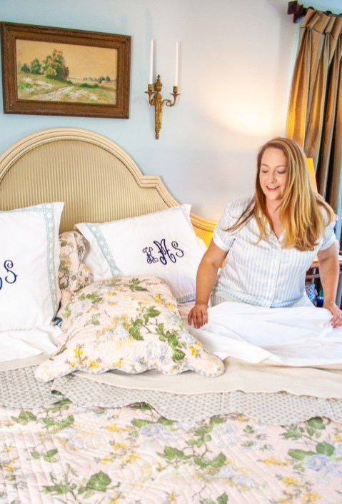 Katherine crawls into freshly made bed with chintz quilt, white sheets, and monogrammed pillows