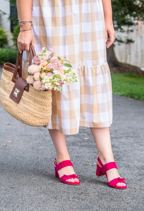 Katherine in gingham dress with straw handbag and sassy pink sandals from Sarah Flint