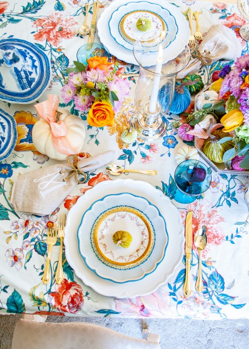 Top view of autumn tablescape with vintage chintz tablecloth, blue china, teal goblets, white pumpkins, blue and white willow dishes, and monogrammed napkins.