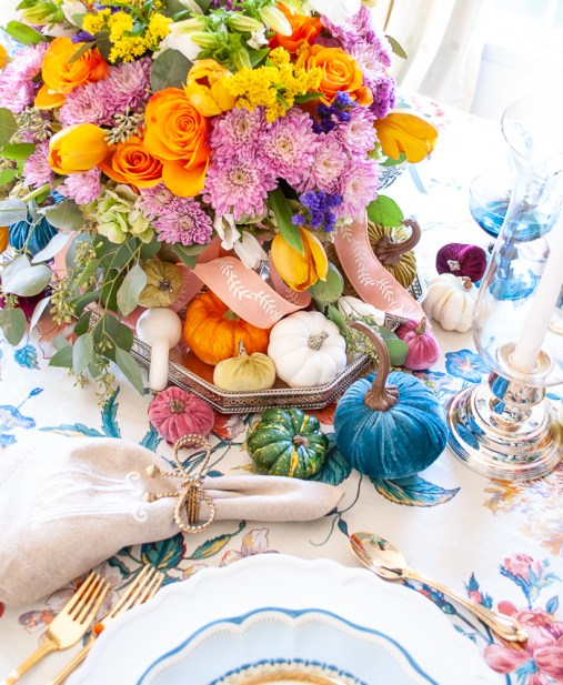 Pumpkins in various sizes, shapes, textures, and colors nestled around floral centerpiece.
