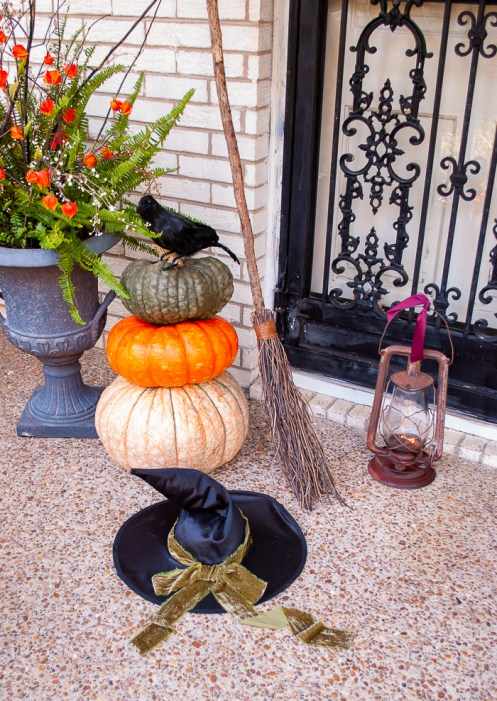 Witches hat, broom, and lantern beside heirloom pumpkin stack with crow give my front door a Halloween vibe