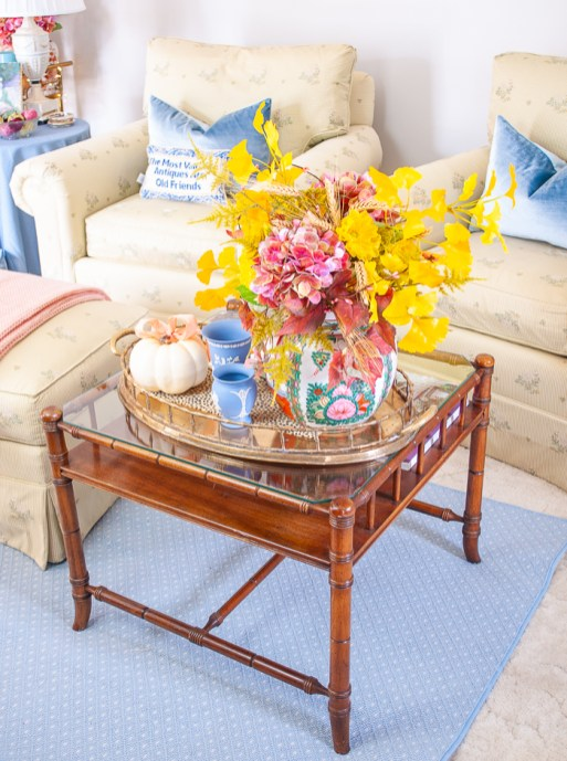 Coffee table with vintage brass tray and fall floral arrangement