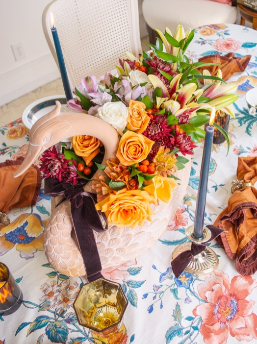 Elegant swan centerpiece with brown velvet bow, orange and white roses, burgundy mums, and lilies add drama to this Thanksgiving tablescape