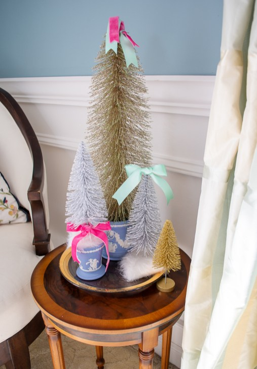 Bold and silver bottle brush trees with pink and green ribbon nestled in Wedgwood Jasperware vases