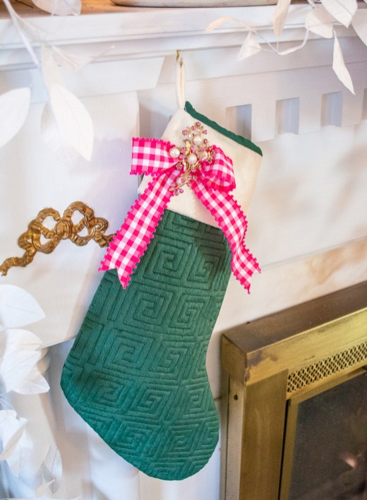 An emerald green Greek key stocking decorated with pink gingham ribbon and vintage brooch