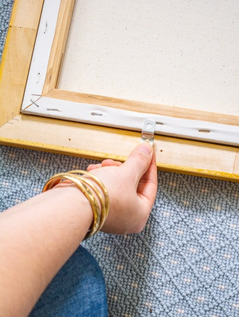How to frame a painting with offset clips and a back-loading frame: here Katherine places a clip at the bottom of the painting and frame.