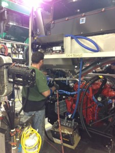 A Gillig worker installs a Cummins engine into a new hybrid SamTrans bus.