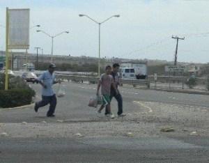 No les importa torear a los carros en la carretera, los desempleados convertidos en vendedores ambulantes corren para vender instalar sus puestos y vender productos en la calle.