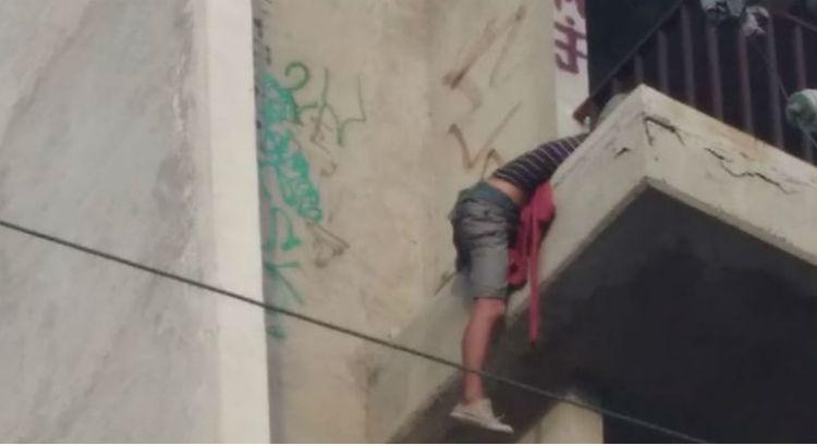 Rescatan municipales a mujer que colgaba de un edificio