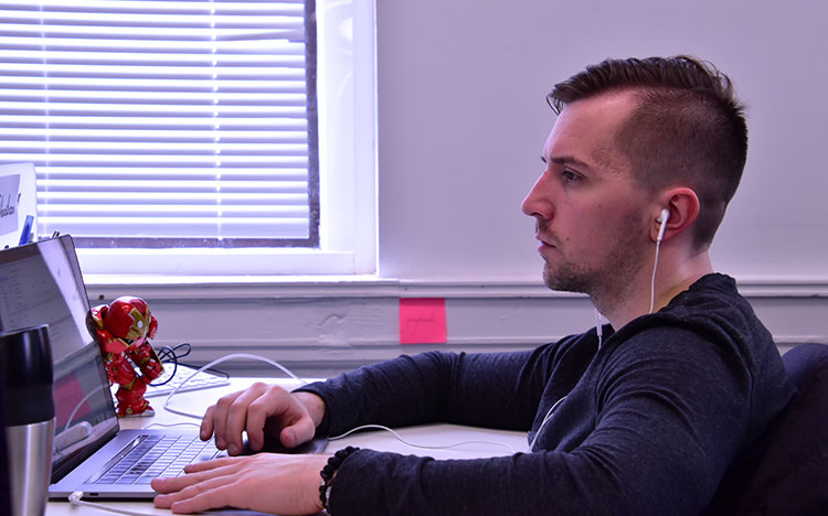 business owner looking at laptop while listening to music