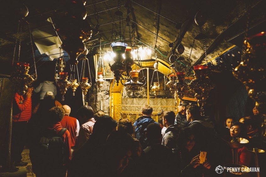 Crowds in the grotto of the Nativity on Christmas Eve. A star marks the spot where Christ was born.