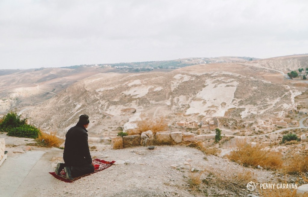 A man praying high above the town at Shobak Castle.